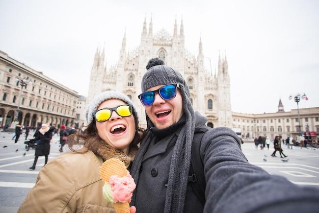 Turista tirando foto de selfie em frente ao famoso duomo de milão