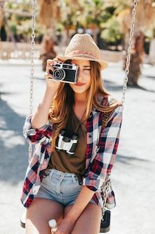 Turista tirando fotos e sentado no balanço