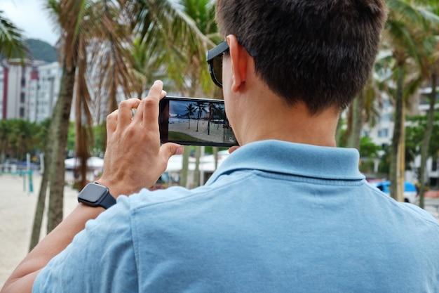Turista tirando fotos no celular de copacabana