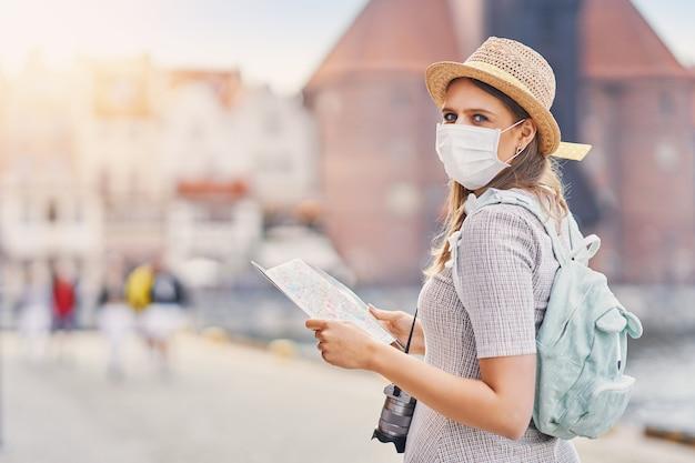 Turista usando uma máscara, visitando gdansk na polônia no verão