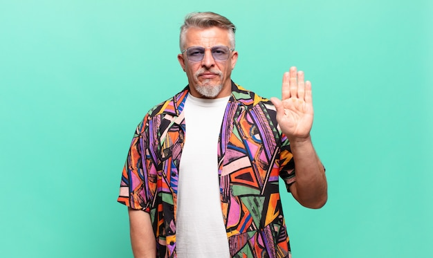 Turista viajante sênior com cara de sério desagradado e irritado, mostrando a palma da mão aberta fazendo gesto de pare
