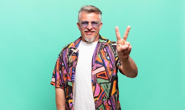 Turista viajante sênior sorrindo e parecendo amigável, mostrando o número dois ou o segundo com a mão para a frente, em contagem regressiva