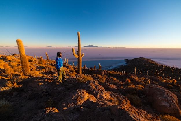 Turista wching nascer do sol sobre uyuni salt fl, bolívia