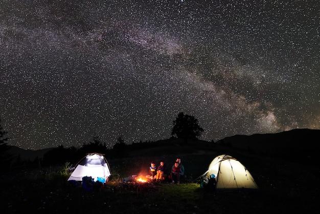 Turistas à noite acampando nas montanhas
