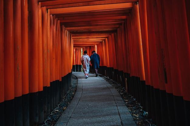 Turistas admirando a estrutura do santuário fushimi inari taisha em kyoto, japão