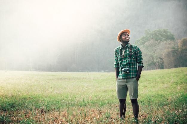 Turistas africanos ficam em meio à natureza, montanhas e névoas, felizes, livres e relaxados. conceito de viagens de aventura