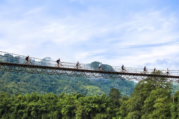 Turistas andando de bicicleta pela ponte suspensa em kanchanaburi, tailândia