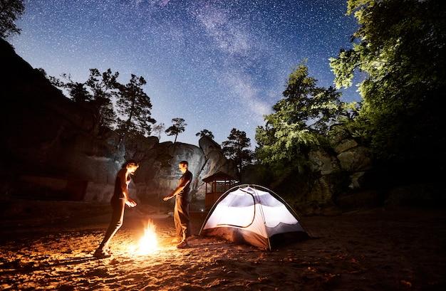 Turistas ao lado do acampamento, barraca da fogueira à noite