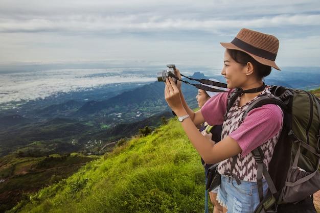Turistas asiáticos das mulheres felizes com fotografia.