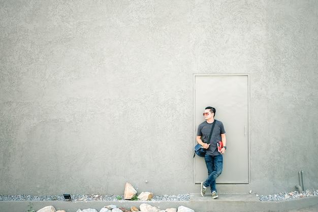 Turistas asiáticos do homem que estão na frente de uma parede cinzenta.