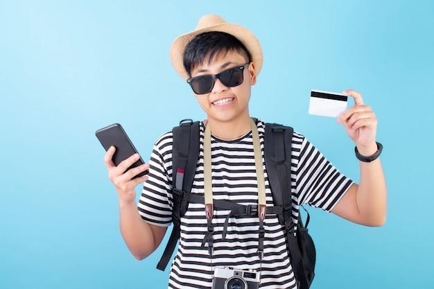 Turistas asiáticos vestindo roupas de verão gostam de fazer compras em seus smartphones com cartão de crédito em um azul