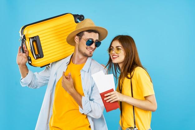 Turistas asparkam e bilhetes de avião férias bagagem viagens divertido jovem casal de óculos azul