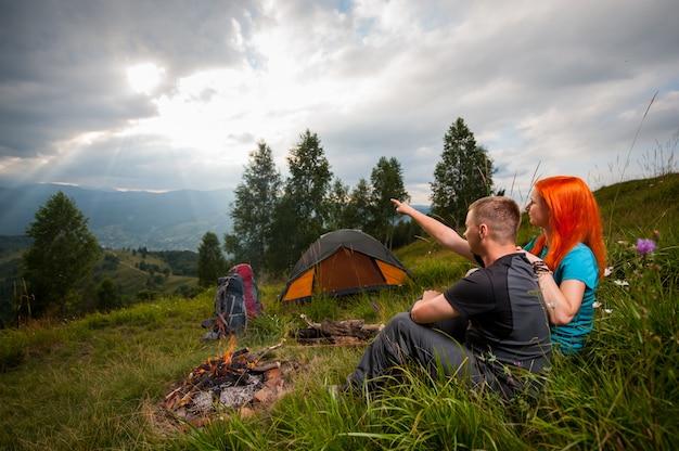 Turistas casal sentado na grama verde perto da fogueira