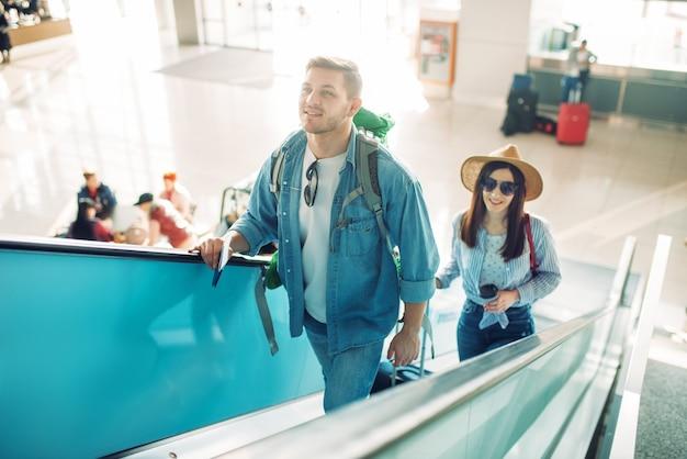 Turistas com bagagem sobem a escada rolante no aeroporto. passageiros com bagagem no terminal aéreo