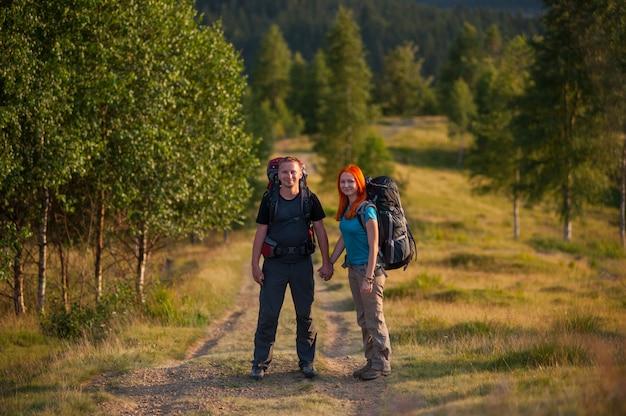 Turistas com mochilas de mãos dadas em uma trilha para a montanha
