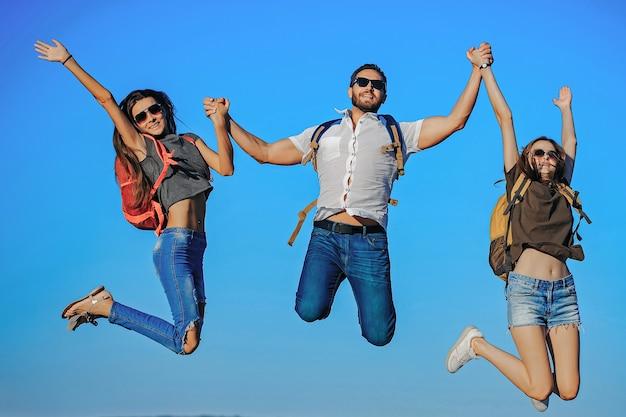 Turistas de amigos felizes pulando no topo de uma montanha no céu azul das férias de verão viajando e caminhando