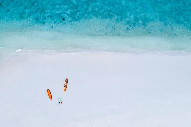 Turistas de caiaque laranja cor pastel na praia de areia Foto Premium
