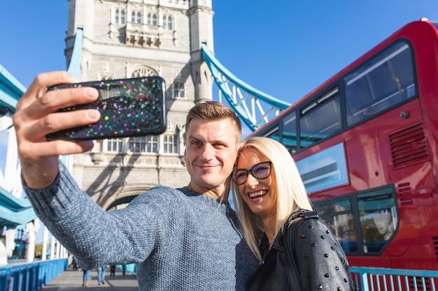 Turistas de casal feliz tomando selfie na tower bridge em londres