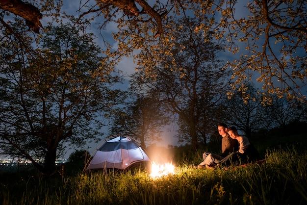 Turistas de casal romântico sentado em uma fogueira perto da barraca, abraçando-se sob árvores e céu noturno. acampamento noturno