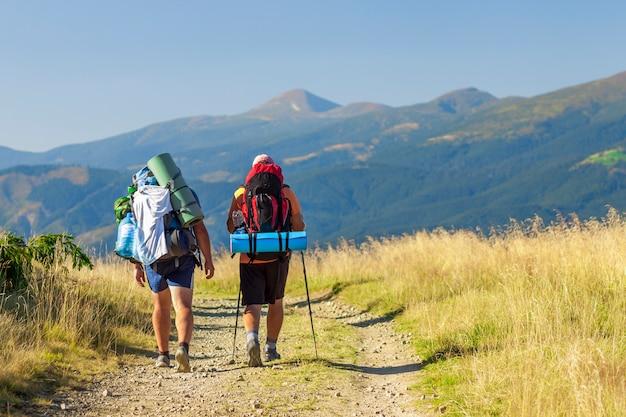 Turistas de dois caminhantes em um caminho nas montanhas