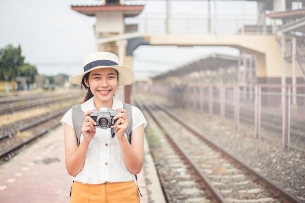 Turistas de mulheres carregando uma câmera de filme e sorrindo brilhantemente na estação de trem