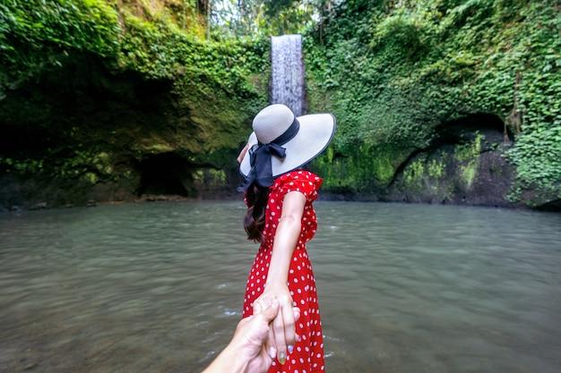 Turistas de mulheres segurando a mão do homem e levando-o à cachoeira de tibumana em bali, indonésia.