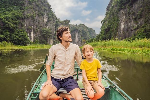 Turistas de pai e filho em um barco no lago tam coc ninh binh vietnã é patrimônio mundial da unesco