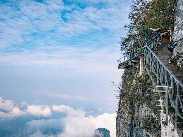 Turistas desconhecidos no penhasco de vidro caminham na montanha tianmen na cidade de zhangjiajie, china. a montanha de tianmen, o destino de viagem da cidade de hunan zhangjiajie, china