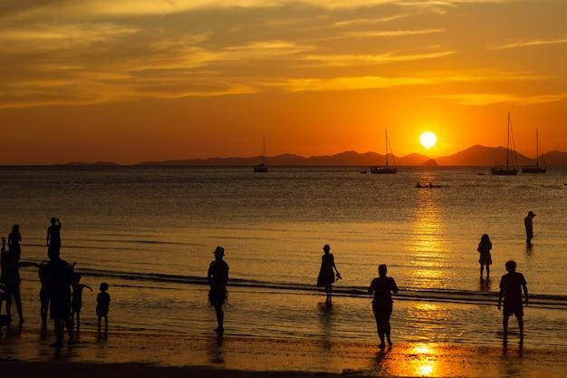 Turistas desfrutam de um lindo pôr do sol em uma praia tropical. silhuetas de pessoas observando o sol