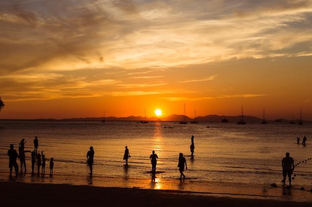 Turistas desfrutam de um lindo pôr do sol na praia tropical. silhuetas de pessoas vendo o sol
