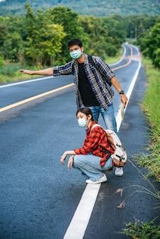 Turistas do sexo feminino sentam-se, turistas do sexo masculino, fingem pedir carona ambos vestindo uma máscara e ao lado da estrada.