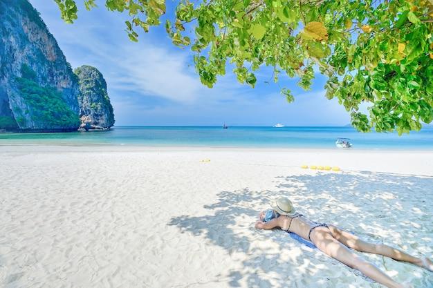 Turistas dormem na praia no mar de krabi