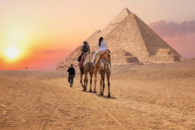 Turistas em camelos perto das grandes pirâmides de gizé, no egito.
