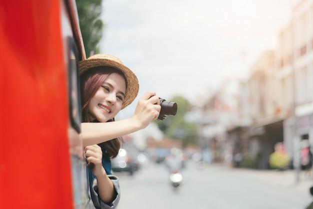 Turistas entusiasmados estão tirando fotos enquanto estão sentados no carro.