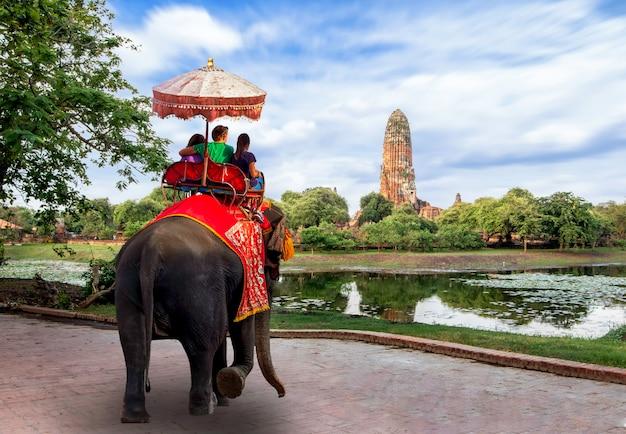 Turistas estrangeiros passeio de elefante para visitar ayutthaya, existem ruínas e templo no período ayutthaya. o conceito é viajar no templo.