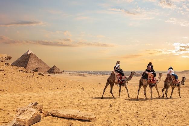 Turistas europeus montando camelos perto das pirâmides do egito.