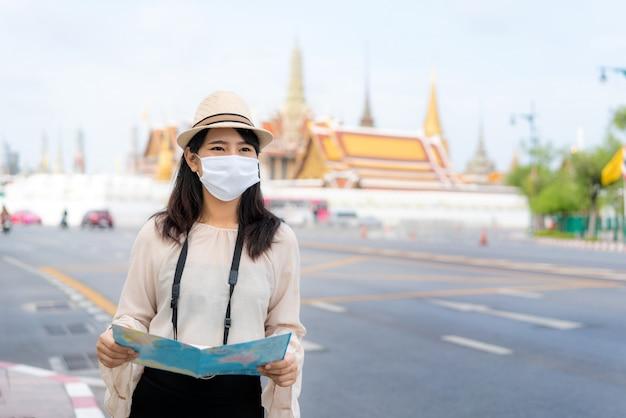 Turistas felizes da mulher asiática para viajar usando máscara