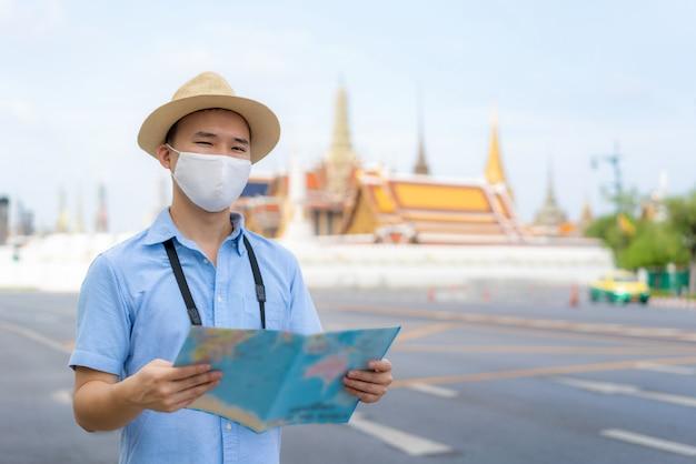 Turistas felizes do homem asiático para viajar usando máscara