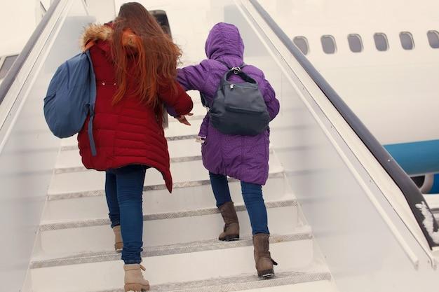 Turistas felizes duas garotas com mochilas sobem no avião escada