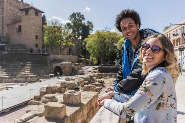 Turistas felizes na frente do monumento romano