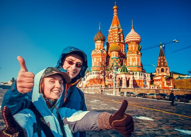 Turistas felizes, passeios pela cidade com os dedos ao lado da catedral de são basílio. praça vermelha, moscou, rússia. férias, viagens, recreação. temporada de inverno, cores brilhantes, céu azul claro