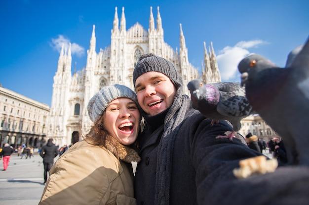 Turistas felizes tirando um auto-retrato com pombos em frente à catedral duomo, em milão.