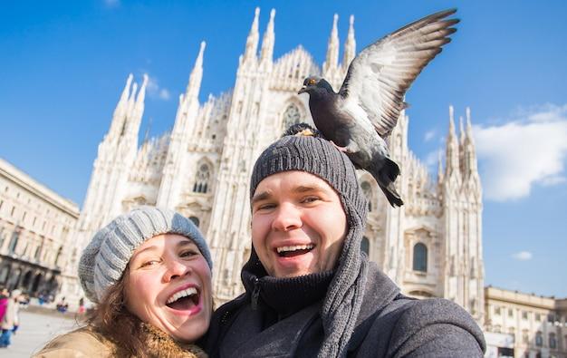 Turistas felizes tirando um auto-retrato com pombos engraçados em frente à catedral duomo em milão.
