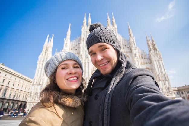 Turistas felizes tirando um autorretrato em frente à catedral duomo