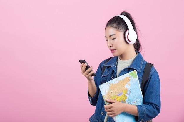 Turistas fêmeas no estúdio em um fundo cor-de-rosa.