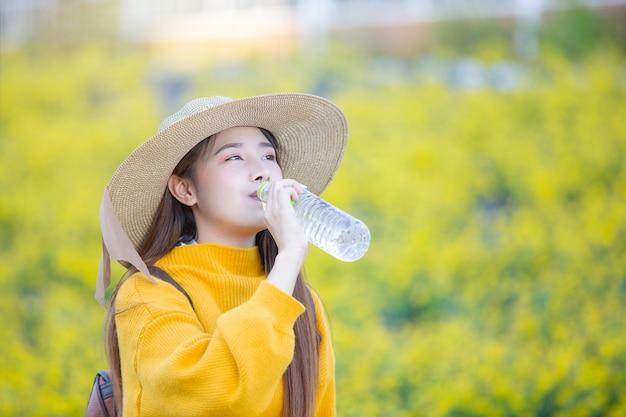Turistas femininos ficam bebendo água enquanto caminhava.