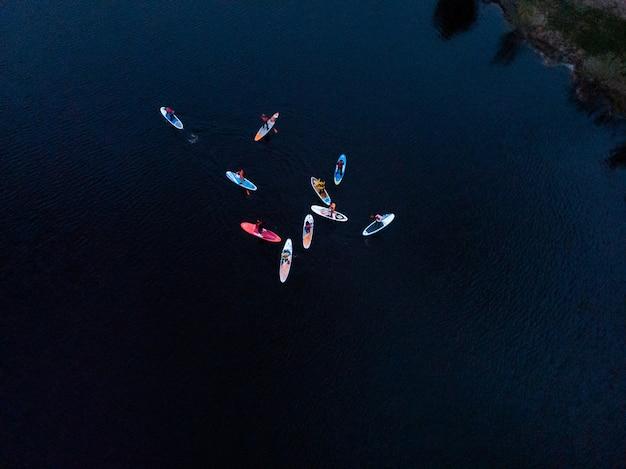 Turistas flutuando na placa de sup no mar azul. vista superior de um grupo de pessoas nas pranchas sup flutuando em um mar calmo e claro
