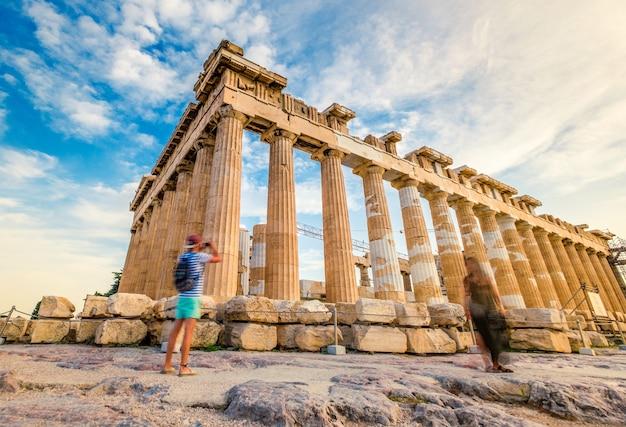Turistas fotografando ruínas de colunas de mármore do partenon