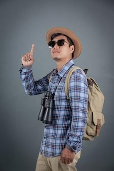 Turistas masculinos que backpacking guardarando o fundo cinzento dos binóculos.