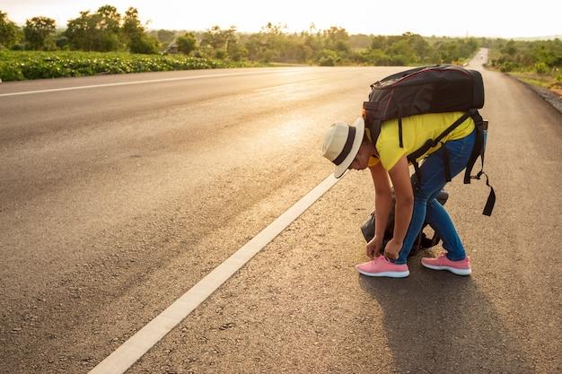 Turistas mulheres, amarrando, a, tênis, ligado, a, rodovia